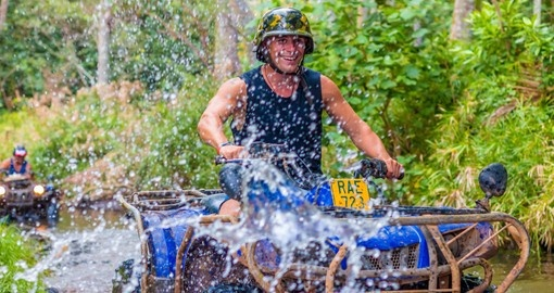 Ride a 4 wheel quad through the streams and wild island jungle during your Cook Islands vacation.