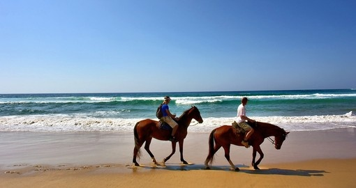 Two horse riders on beach in Sodwana Bay Nature Reserve