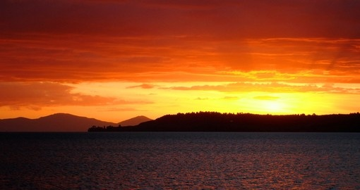 Experience Red sunset over Lake Taupo during your next New Zealand tours.