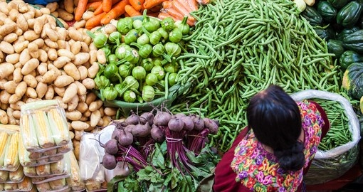 Woman sells vegetables at a traditional weekly market
