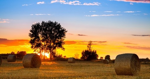 End of the day over field with hay bale