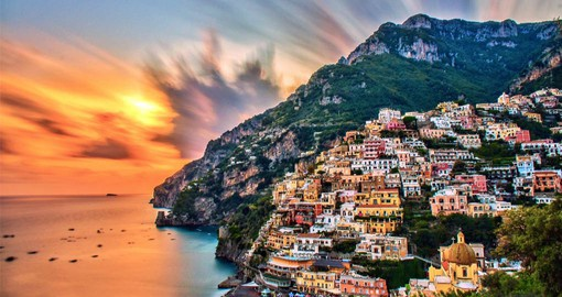 Take in a sunset off the coast of Positano on your Italy vacation