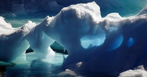 Exploring massive Ice Caves in the icy cold waters of Antarctica on your Antarctic Vacation Package