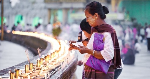 Buddhist devotees lighting candles during full moon festival