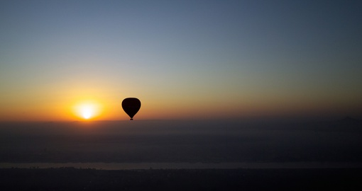 A hot air balloon with the rising sun at dawn over the Nile River