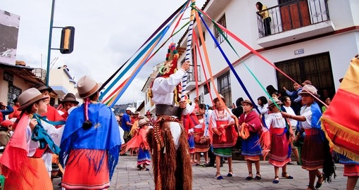 Indigenous group dancing around pole in traditional costume
