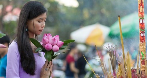 Young Vietnamese woman offering flowers at Buddhist shrine
