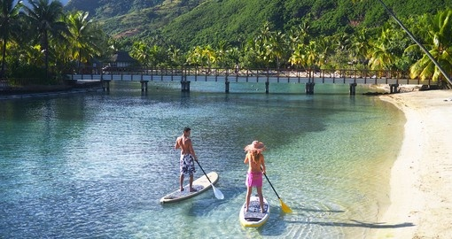 Couple paddling along the beach at the Intercontinental Moorea