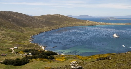 An idyllic bay in the Falkland Islands with a farmhouse and cruise ship