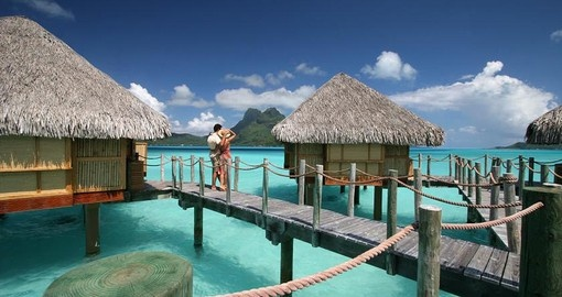 Stroll along the wooden walkways connected to the overwater bungalows during your Trips to Tahiti.