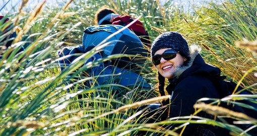 Girl hiking through tussock grass