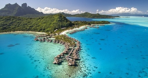 Explore aerial view of the beautiful 5-star Conrad Bora Bora Nui with mount otemanu in the backdrop during your Bora Bora Vacation.