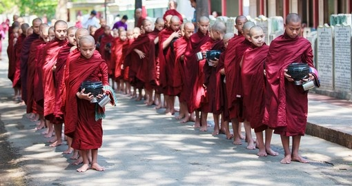 Young Buddhist monks walk to collect alms and offerings in the Monastery