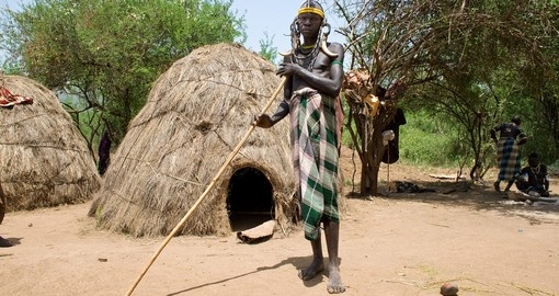 Man of the Mursi tribe in front of his hut