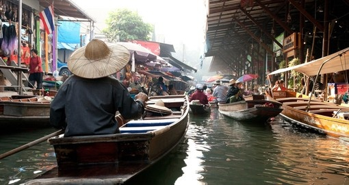 Learn about traditional culture and practices while floating on wooden boats in the floating market on you Thailand Vacation