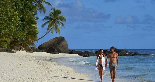 Enjoy a romantic stroll along the beach during your trip to Seychelles.