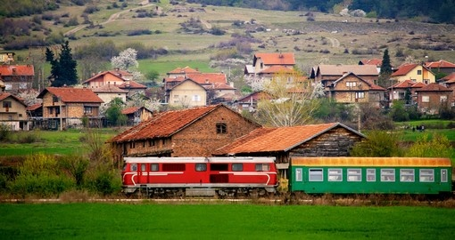 Bulgarian train passing through spring green meadows near small village