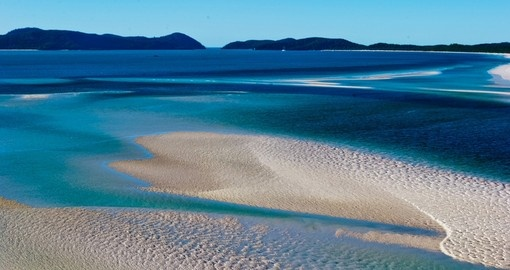 Take a walk or have a sunbathe on white sand in the Whitsundays during your next Australia tours.