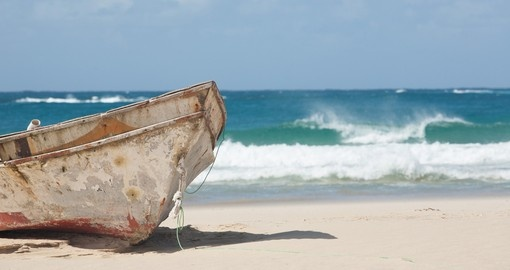 Old fishing boat on the beach. The waves of the Indian Ocean breaking on the beach of Barra in Mozambique