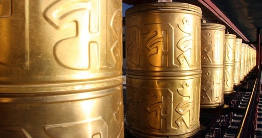 Row of Buddha copper prayer wheels