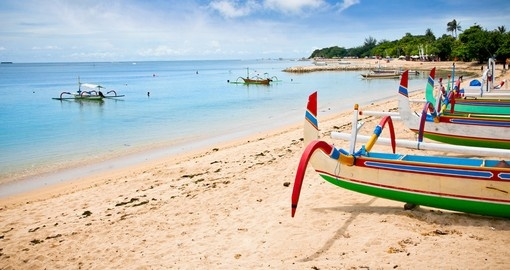View traditional fishing boats on a beach in Nusa Dua on your Bali vacation