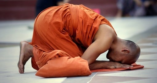 Buddhist monk kneels down in prayer