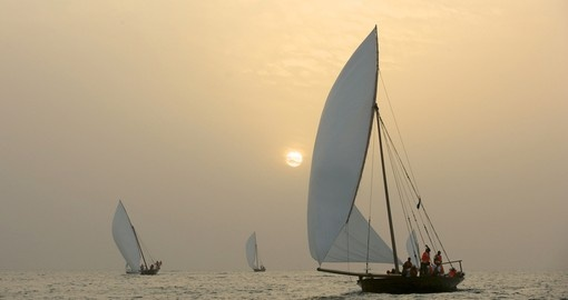 Traditional Dhows sailing in the Arabian Gulf, off Dubai, at sunset