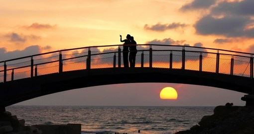 Silhouettes of two people standing on a bridge