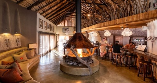 Cozy up next to the fireplace at the Impodimo Game Lodge during your South Africa trip.