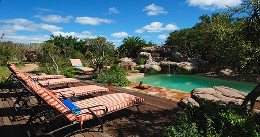 Lounge by the pool at the Ukhozi Lodge during your South Africa trip.