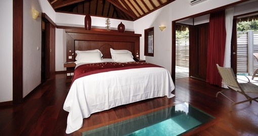 Enjoy a spacious room with a partial glass floor in your overwater bungalow during your Tahiti Vacations