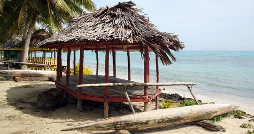 Huts and boat on a sandy beach on Savaii