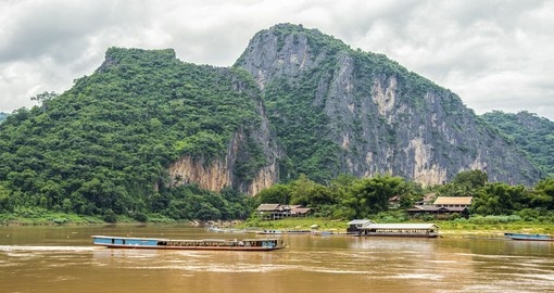 Enjoy the natural forests and mountains that surround the Mekong river on your Laos Vacation