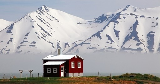 Beautiful, cosy houses add colour to the Iceland dramatic landscape.