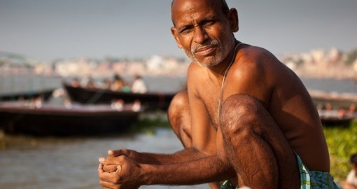 Man bathe at the edge of the Ganges