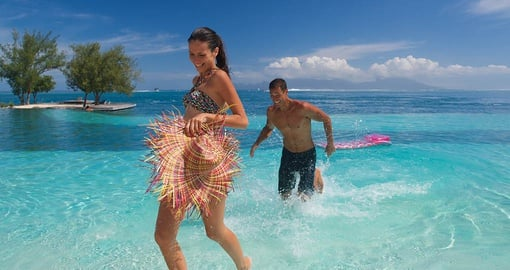 Couple jumping in the water of Tahiti