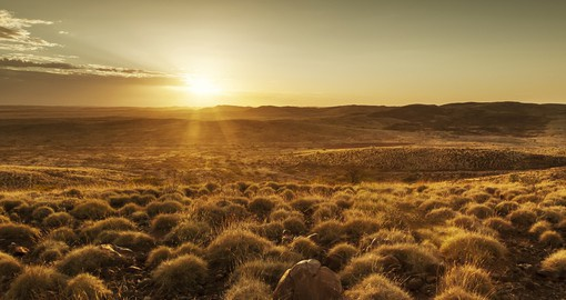 Gaze up at the sunrise in the Australian Outback first thing in the morning and enjoy the dry desert heat