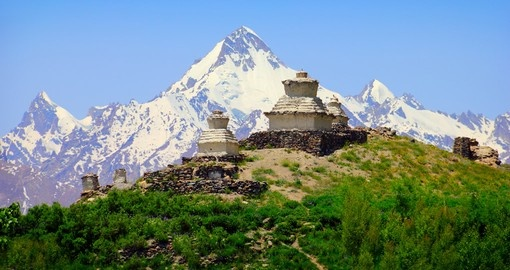 Beautiful scenic view - green hill with old white buddhist stupa against the background of colorful mountain range covered with snow and blue sky