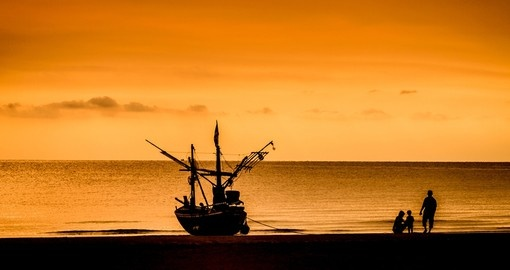A fishing boat and family at sunset in Hua Hin