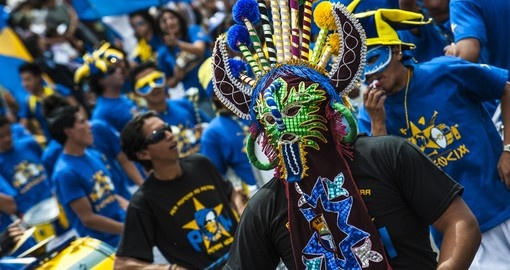 Ecuadorean masks dance as part of a parade through the street