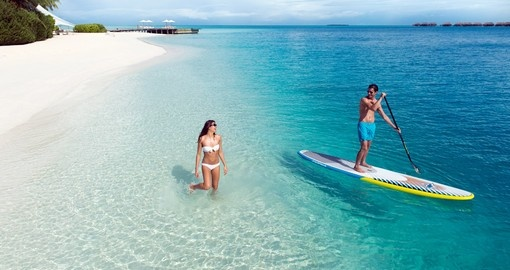 Cruise along the crystal clear waters on a paddle board on your Maldives Vacation