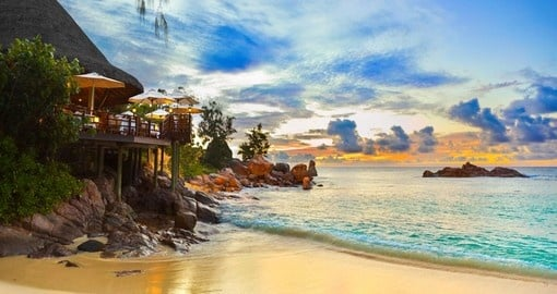 A cafe overlooking a tropical beach at sunset in the Seychelles Islands.