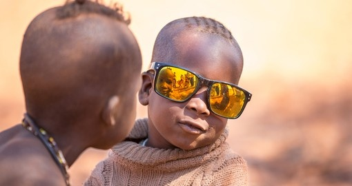 Himba child poses with sunglasses