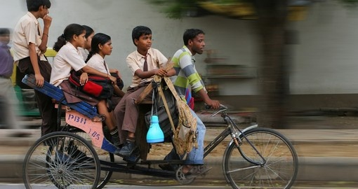 An Indian family riding a cycle rickshaw