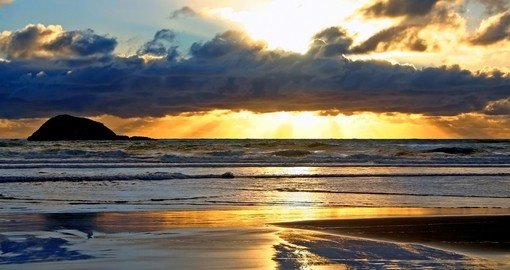 Enjoy a beautiful sunset at Maori Bay during your next New Zealand vacations.